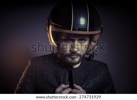 Motorbike, biker with motorcycle helmet and black leather jacket, metal studs - stock photo