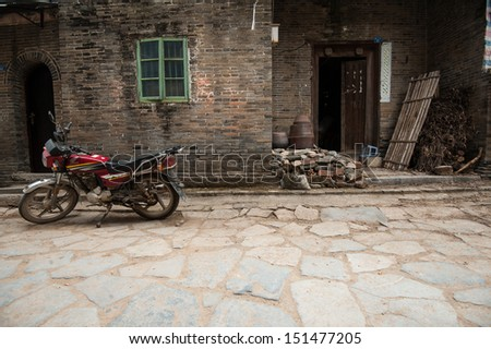 Motorbike cart parked in front of the decaying facade, China - stock photo
