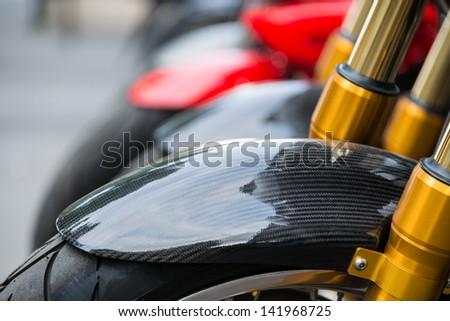 Motorbike detail, carbon fiber mud guard and golden dampers - stock photo