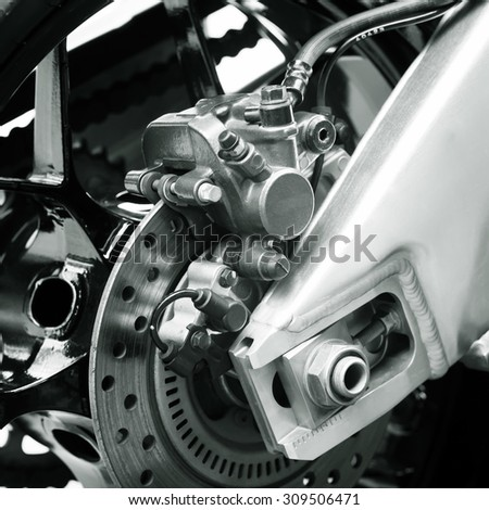 Motorbike engine disk brake,A black and white photo.