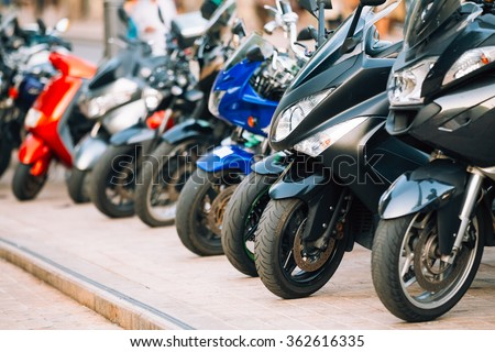 Motorbike, motorcycle scooters parked in row in city street. Close up of wheel - stock photo