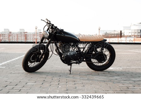 Motorbike. Road and city with open sky on background. Vintage custom motorcycle - stock photo