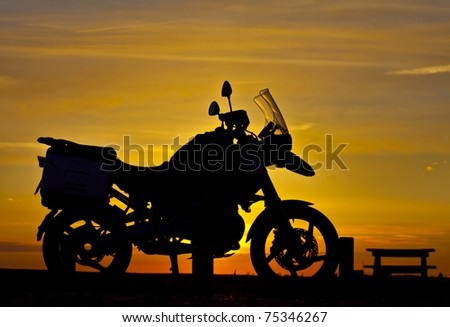 Motorbike Silhouette a motorbike stands on the beach with a sunset behind creating a silhouette of the machine - stock photo