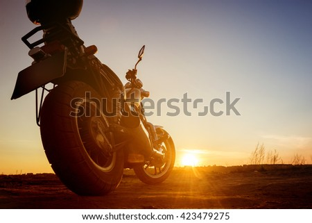 Motorbike stands on sunset backdrop  - stock photo