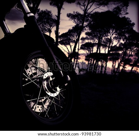 Motorbike wheel over forest sunset, selective focus on part of bike, shiny tire details, outdoor adventure ride, summer fun trip, freedom lifestyle concept - stock photo