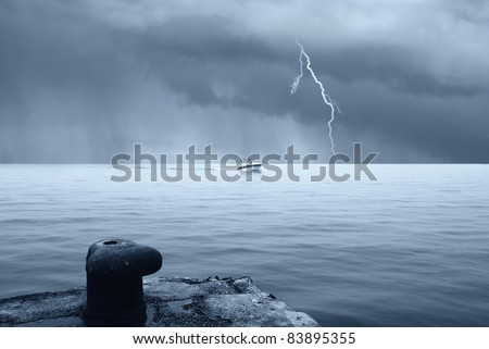 motorboat in the sea with stormy sky with lightning - stock photo