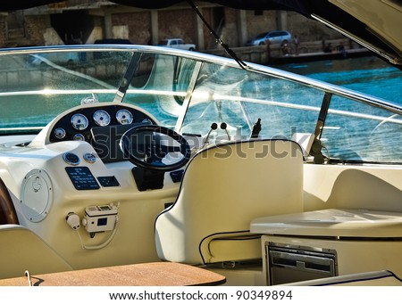 Motorboat - interior with navigators cabin. View from yacht cockpit at the sea harbor. - stock photo