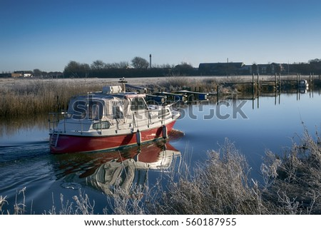 Motorboat sailing on Ribe River in Wadden Sea National Park, Denmark.