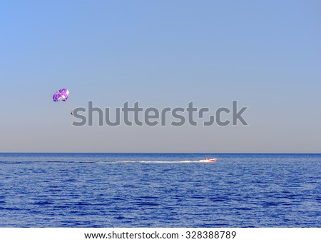 Motorboat towing a parasail parachute with a suspended person in a harness high in the air across a calm blue ocean in evening light - stock photo