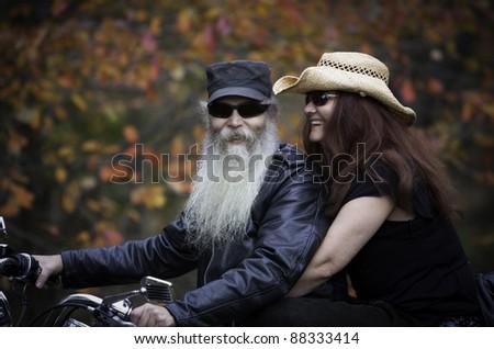 Motorcycle biker couple ride their bike in autumn season - stock photo