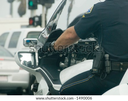 Motorcycle cop showing communication tools on belt - stock photo