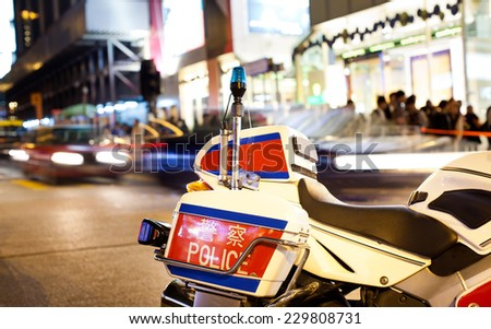 Motorcycle cop standing in the middle of the road - stock photo