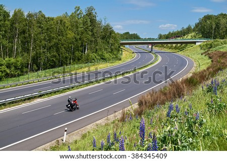 Motorcycle driving on the empty highway with a double bend in a rural landscape. The bridge over the highway. View from above. Sunny summer day with blue skies and white clouds. - stock photo
