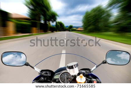Motorcycle going at high speed on a straight road - stock photo