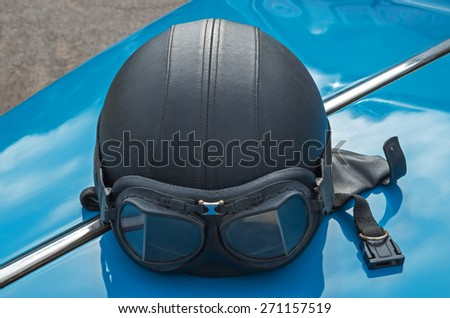 Motorcycle helmet with skin lies on the hood of a retro car. - stock photo