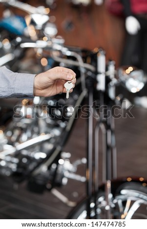 Motorcycle key. Close-up image of hand holding key with motorcycle on the background - stock photo