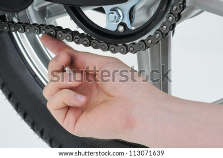 motorcycle mechanic checking the tension on a chain - stock photo
