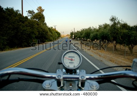 Motorcycle on road from rider's perspective with cyclists ahead. Shallow DOF, focus on cyclists. - stock photo