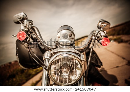 Motorcycle on the road with a helmet on the handlebars. - stock photo