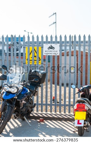 Motorcycle parking sign mounted on a metal fence - stock photo