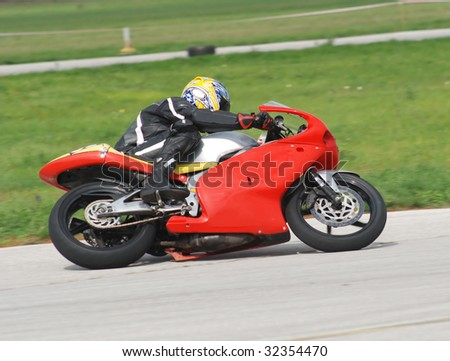 Motorcycle races, red motorcycle in full speed - stock photo