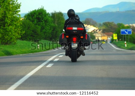 Motorcycle rider riding down a lonely country road - stock photo