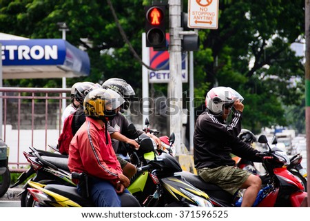 Motorcycle Riding Commuters Wait at a Stop Light Intersection in Manila, Philippines - July, 2015. - stock photo