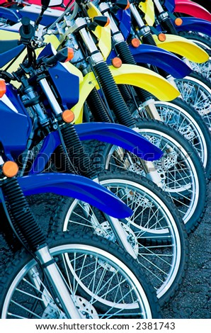 Motorcycles in a row with brightly colored fenders, ready to be sold. - stock photo
