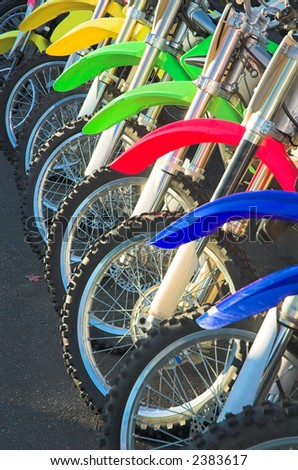 Motorcycles in a row with brightly colored fenders ready to be sold. - stock photo