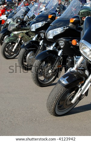 Motorcycles stand in a line on road