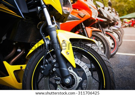 motorcycles standing in the row on asphalt closeup - stock photo