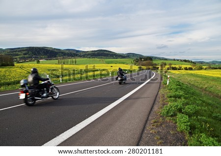 Motorcycles traveling along an empty asphalt road between yellow blooming rape fields in the rural landscape. In the background of forested mountains. - stock photo