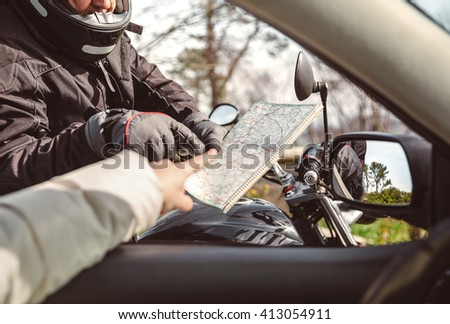 Motorcyclist asking to map direction - stock photo