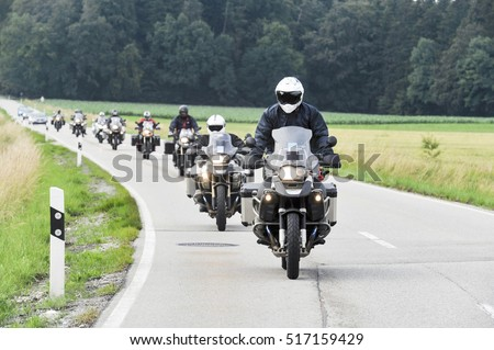Motorcyclist convoy pass through country road
