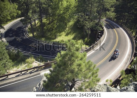 Motorcyclist driving on Iron Mountain Road, Black Hills, near Mount Rushmore National Memorial, South Dakota - stock photo