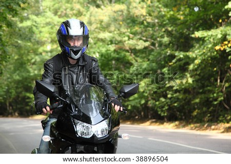 motorcyclist goes on road - stock photo