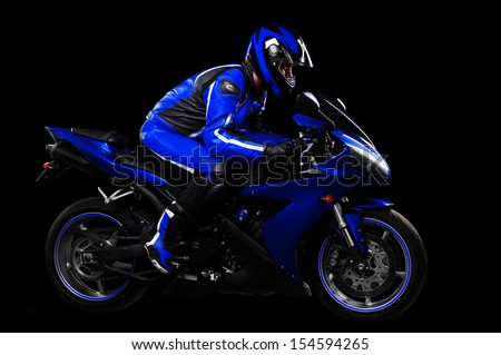 Motorcyclist in blue equipment and helmet on black background side view full length - stock photo