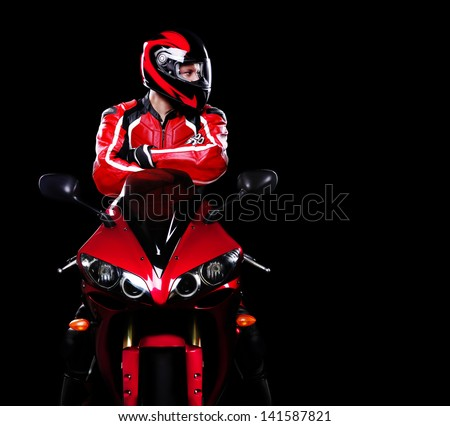 Motorcyclist in red equipment and helmet on black background looking to the copy space area - stock photo