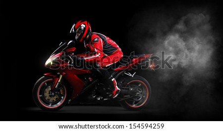 Motorcyclist in red equipment and helmet on black background side view full length - stock photo