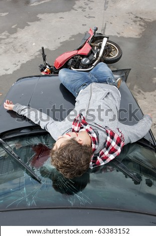 Motorcyclist is being hit by a car, and lies unconsciously on the smashed windscreen, bleeding heavily - stock photo