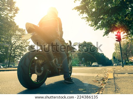 Motorcyclist on the road - Racing motorbike stops at traffic lights at sunset - stock photo