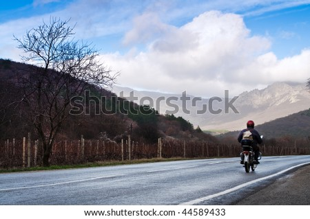 motorcyclist on the rural road - stock photo