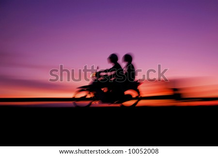 Motorcyclist travels while sunset on Highway - stock photo