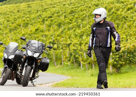 Motorcyclist with helmet walks on the road - stock photo