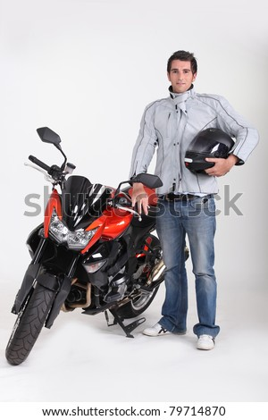Motorcyclist with his motorbike - stock photo