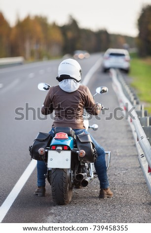 Motorcyclist woman traveling on asphalt road, rear view