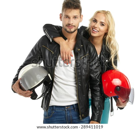 motorcyclists couple with helmets in hand - stock photo