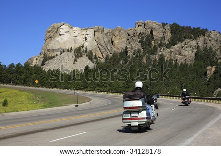Motorcyclists drive on the road to Mount Rushmore National Memorial, South Dakota. - stock photo