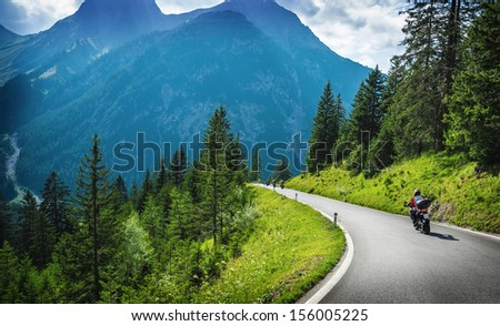 Motorcyclists in mountainous touring, extreme adventure, European journey, extreme road along Alps, active holiday concept - stock photo