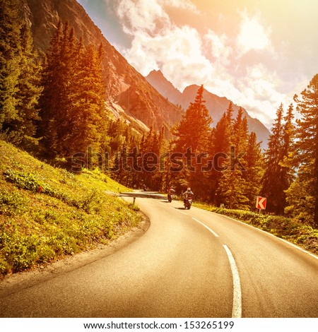 Motorcyclists on the mountainous road in bright red sunset light, riding on highway pass along Alpine mountains, enjoying extreme sport, travel and tourism - stock photo